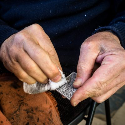 Preparing a sidewalk cobblestone coaster with the most famous pattern, Mar Largo (Large See), under the arches of Praça do Comércio